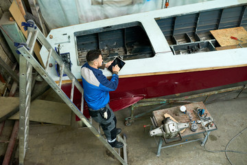 High angle portrait of modern worker using digital tablet while repairing boat in yacht workshop, copy space