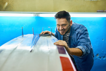 Portrait of handsome modern man  smiling happily while carefully polishing handmade surfing board with felt disk in yacht workshop, copy space