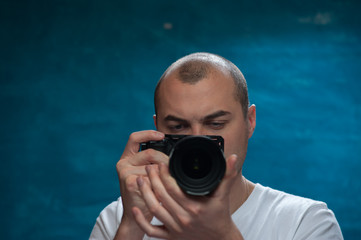 Setting the camera. Male professional photographer holding camera in hands posing over blue studio background