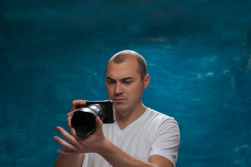 Young man wearing casual clothes using professional camera posing on blue vintage background