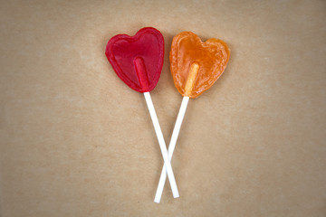 Couple of heart shape lollipops on a cardboard
