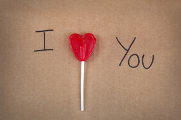 I love you message written a heart shape lollipop on a cardboard