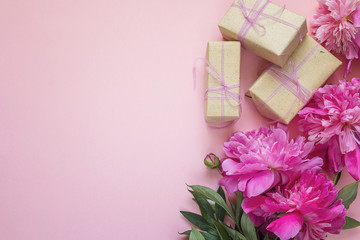 Romantic background with peonies and gift boxes on pink.
