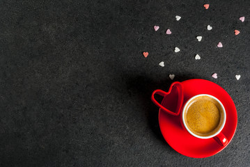Valentine's day concept, coffee mug and sweet heart shaped sprinkles, black background, copy space  top view