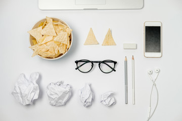 Workspace with laptop, crumpled paper, stationery and chips on white table. Bad habits concept