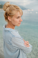 Young beautiful blonde woman in striped shirt on sea background. Summer concept