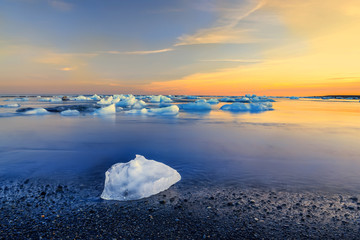 Coast of the Atlantic Ocean. The ice floe on a black sandy beach and floating ice floes in the water at sunset. Long exposure. Iceland.
