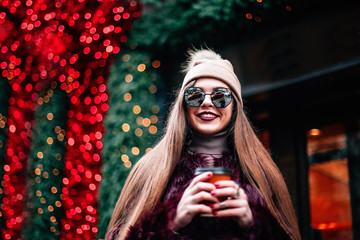 young stylish girl in burgundy coat and knitted hat holds in hands coffee dressed in sunglasses smiling at camera