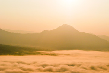 Early morning foggy sunrise on top of mountain soft focus.