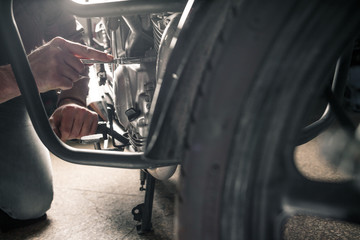 Close up of man's hands with motorcycle in garage