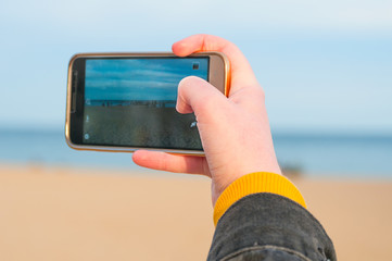 Female hand making photo of beach with mobile phone