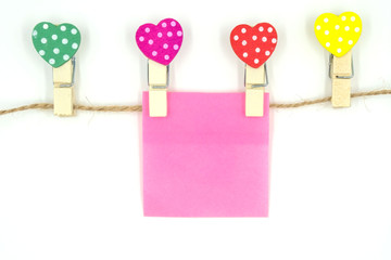 colorful clothespin with heart shape design and pink  paper sheet and rope for valentine concept isolated on white background . Space for text and images .