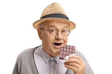 Mature man having a bite out of a chocolate bar