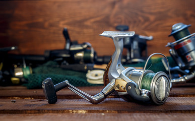 Fishing tackles on a wooden table close up. At a background a spinning, fishing accessories