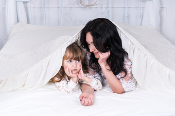 Mother and daughter lie under the blanket on the big bed in the bedroom