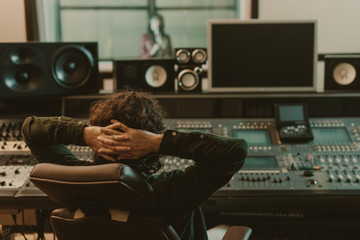 Fototapeta sound producer relaxing in armchair at recording studio obraz