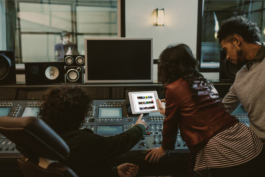 sound producers using tablet together at recording studio with youtube website on screen