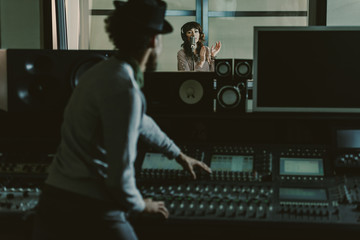 sound producer in hat recording song at dark studio