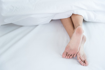 Under white blanket covers with feet showing