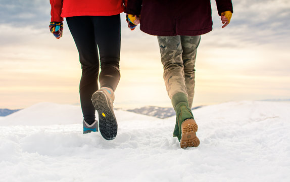 Friends hiking on the mountaintop covered with snow