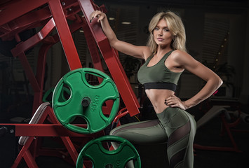 Young beautiful blond girl with idyllic abdominal muscles athlete bodybuilder in sports clothes, resting after individual coaching with a trainer in a weightlifting gym.