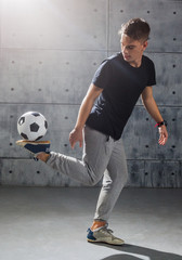 Football freestyle. Young man practices with soccer ball