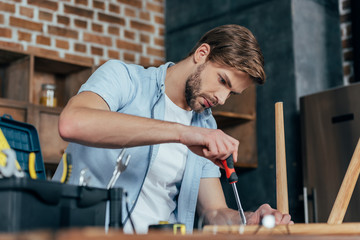 focused young man repairing stool with screwdriver