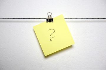 Zettel mit einem Fragezeichen aufgemalt hängt an einer Leiste