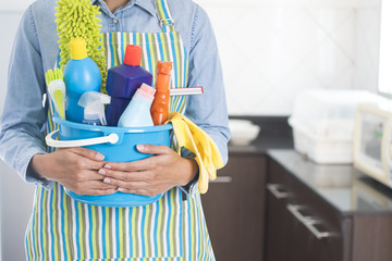 woman with cleaning equipment ready to clean house on kitchen background