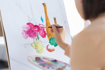 artist with brush painting still life at studio