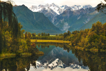 Lake Matheson walking track, reflection of the mountains in pristine clear water lake near Fox Glacier in New Zealand's West Coast, South Island