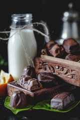 Milk in glass jar with orange and chocolate sweets. Dark wall at background, copy space.