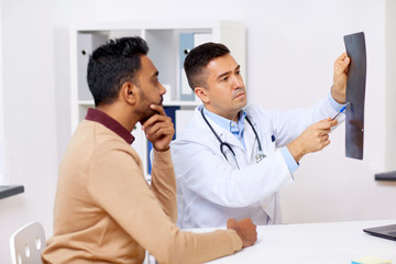 doctor with x-ray and male patient at clinic