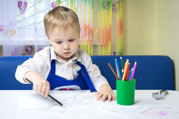 cute pensive caucasian boy 3 years old drawing with colored pencil in a notebook sitting at a desk in a classroom in a kindergarten (play room)