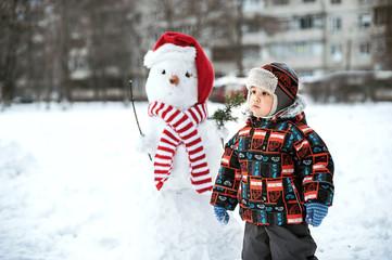 Happy beautiful child building snowman in garden, winter time,