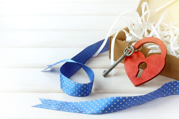 holiday day of all lovers/ heart symbol and padlock with a key next to an open gift on the table