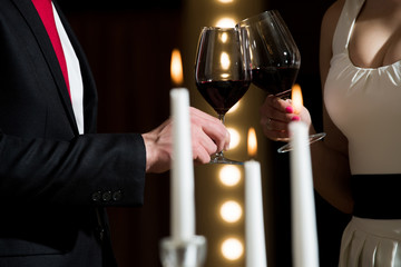 clink glasses with red wine of couple at meeting