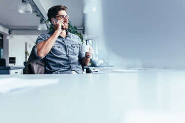 Young man with cup of coffee and talking on cellphone