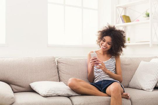Young girl using mobile phone on sofa