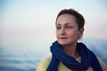 Portrait of happy older woman relaxing on a luxury cruise liner boat deck. Beautiful sunset or sunrise blurred background. Cruise vacation trip concept.