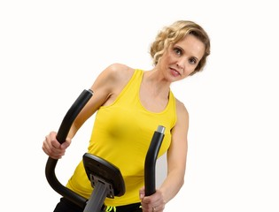 Fit woman on exercise bike on white