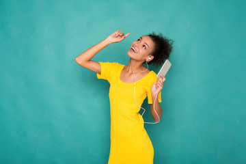 Woman listen to music in earphones, studio shot