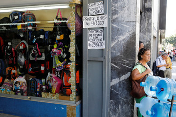Handwritten signs displaying the current prices of clothes are seen at the entrance of a store in downtown Caracas