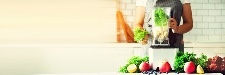 Woman blending lettuce leaves, spinach, aplles, berries, bananas. Homemade healthy green smoothie. White kitchen design. Sunny morning with sunlight. Toned effect. Banner