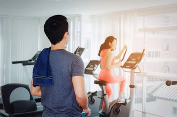 muscular young asian man with towel looking to asian young woman slim body exercising on bicycle machine in fitness gym, bodybuilder, healthy lifestyle, fitness, workout and sport training concept