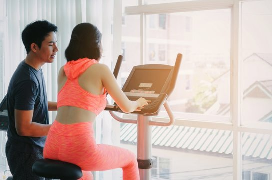 asian young woman slim body exercising on bicycle machine with young man personal trainer in fitness gym, bodybuilder, healthy lifestyle, fitness, workout and sport training concept, soft focus