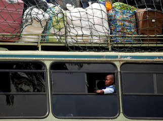 A child sits inside a bus on its way to a boarding school on the opening day of the new school term in Mbare township, Harare