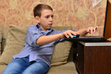 Vertical image of young boy in shirt using laptop computer and sitting on books. Isolated gray background