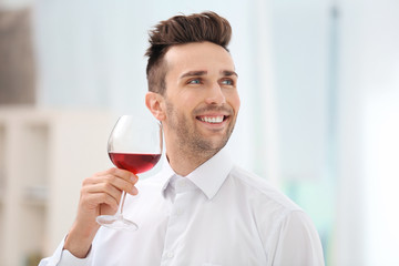Handsome young man drinking red wine indoors