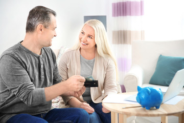 Mature couple with money at home